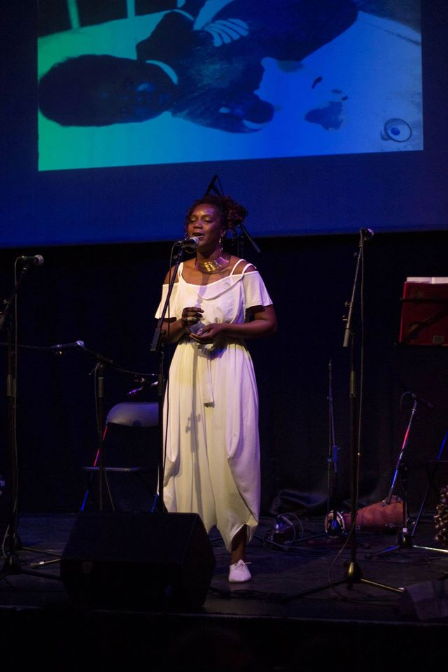 Sonia singing a lullaby from Benin, with a photo above of herself as a baby